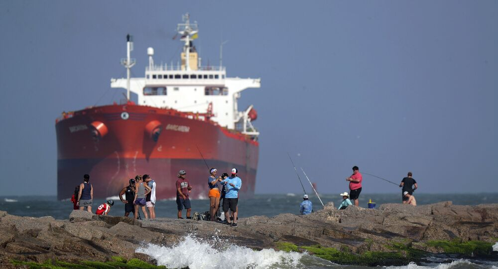 An oil tanker passes a group of people fishing in Port Aransas, Texas. Hundreds of tankers are storing oil that nobody wants.