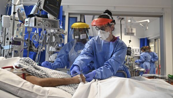 Members of the clinical staff wearing Personal Protective Equipment PPE care for a patient with coronavirus in the intensive care unit at the Royal Papworth Hospital in Cambridge, England, Tuesday May 5, 2020 - Sputnik International