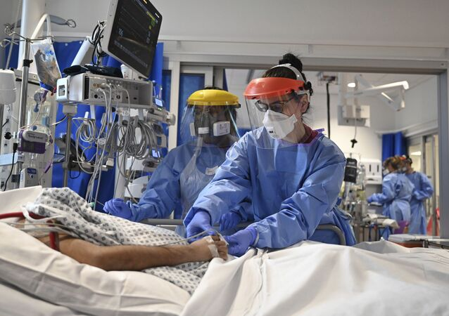 Members of the clinical staff wearing Personal Protective Equipment PPE care for a patient with coronavirus in the intensive care unit at the Royal Papworth Hospital in Cambridge, England, Tuesday May 5, 2020