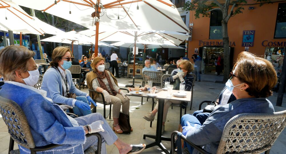 People take a coffee in a bar as some Spanish provinces are allowed to ease restrictions during the phase one, amid the coronavirus disease (COVID-19) outbreak, in Palma de Mallorca, Spain, May 11, 2020. REUTERS/Enrique Calvo
