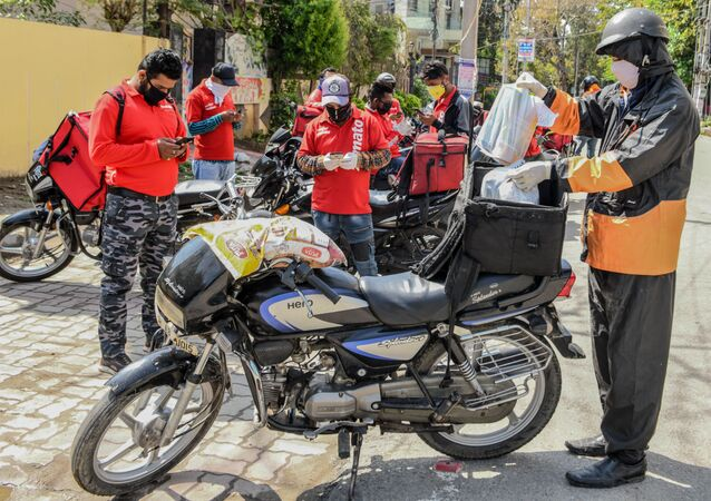 A Swiggy delivery man (R) wearing a facemask puts food commodities in the bag tied to his motorbike to deliver to customers as other Zomato delivery men check their mobile phones during a government-imposed nationwide lockdown as a preventive measure against the COVID-19 coronavirus, in Amritsar on March 28, 2020