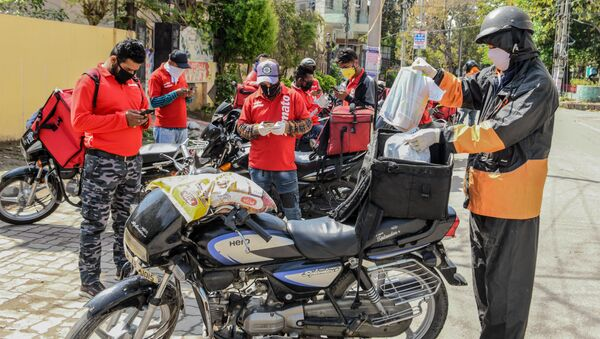 A Swiggy delivery man (R) wearing a facemask puts food commodities in the bag tied to his motorbike to deliver to customers as other Zomato delivery men check their mobile phones during a government-imposed nationwide lockdown as a preventive measure against the COVID-19 coronavirus, in Amritsar on March 28, 2020 - Sputnik International
