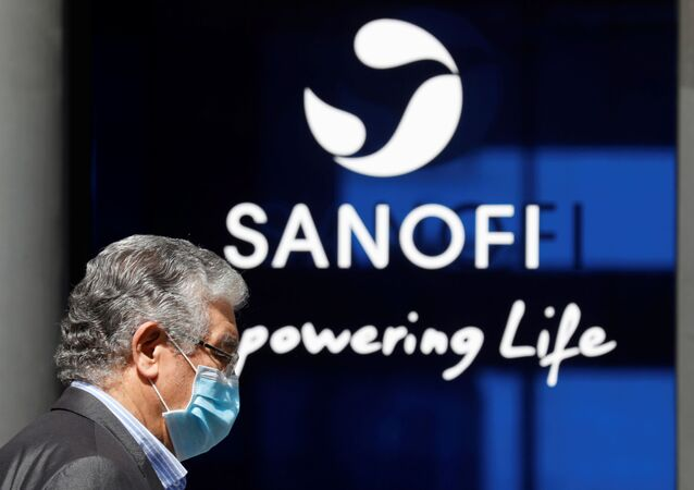 A man wearing a protective face mask walks past the logo of Sanofi at the company's headquarters in Paris, France, April 24, 2020. R