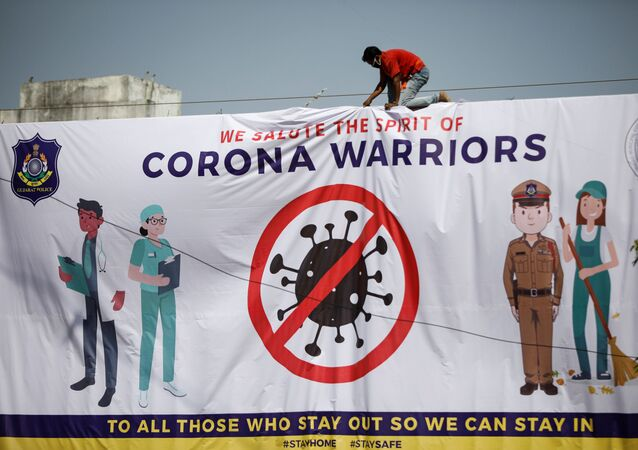 A worker installs a hoarding thanking frontline workers during a nationwide lockdown to slow the spreading of the coronavirus disease (COVID-19), in Ahmedabad, India,