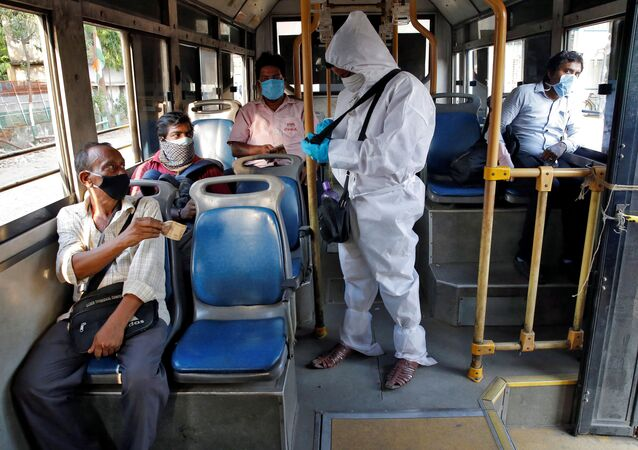 A bus conductor wearing a protective gear issues tickets to passengers maintaining safe social distance on the bus, after the state government resumed public bus service on limited routes after nearly seven-week lockdown to slow the spreading of the coronavirus disease (COVID-19), in Kolkata, India, May 14, 2020.