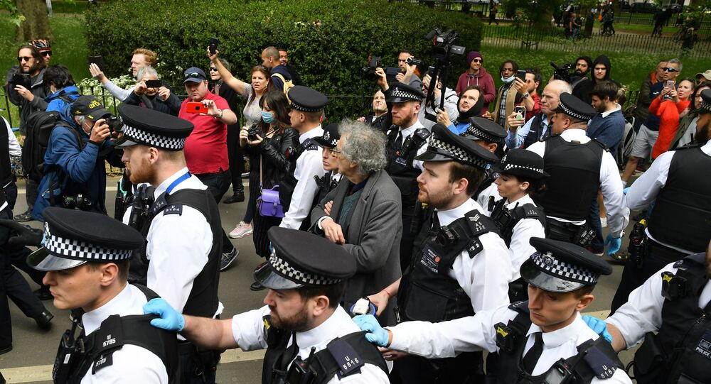 Piers Corbyn (C), brother of former Labour Party leader Jeremy Corbyn, is arrested by police officers at an anti-coronavirus lockdown demonstration in Hyde Park in London on May 16, 2020, following an easing of lockdown rules in England during the novel coronavirus COVID-19 pandemic.