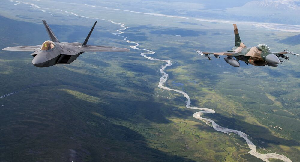 A US Air Force F-22 Raptor from Joint Base Elmendorf-Richardson and an F-16 Fighting Falcon from Eielson Air Force Base fly in formation over the Joint Pacific Alaska Range Complex, July 18, 201