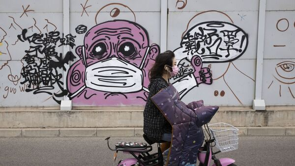 A woman wearing a mask against the coronavirus rides past graffiti with the words Wear your mask properly in Beijing on Friday, May 15, 2020. - Sputnik International