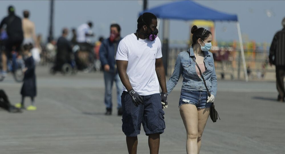 Pedestrians wear protective masks during the coronavirus pandemic while walking on the boardwalk of Coney Island Beach Friday, May 15, 2020, in the Brookyn borough of New York