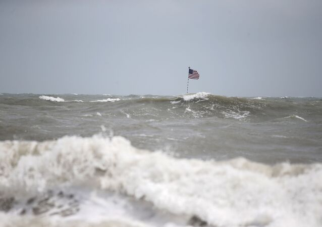Waves crash in front of an American flag that is planted on a jetty during a high surf from the Atlantic Ocean, in advance of the potential arrival of Hurricane Dorian, in Vero Beach, Fla., Monday, Sept. 2, 2019.