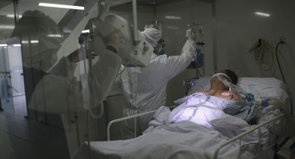 Members of medical staff, wearing protective suits and face masks, do a lung X-ray on a patient suffering from coronavirus disease (COVID-19) in the Intensive Care Unit (ICU) at a field hospital set up to treat patients suffering from the disease (COVID-19) in Guarulhos, Sao Paulo state, Brazil