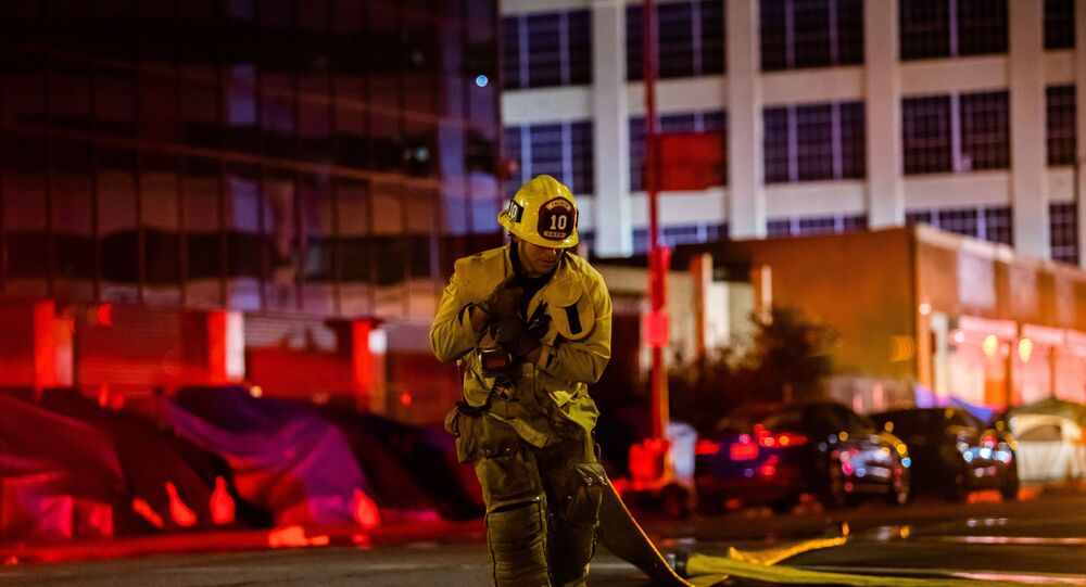 A firefighter drags a hose on San Pedro Street after a fire in a single-story commercial building sparked an explosion in the Toy District of downtown Los Angeles on May 16, 2020. - At least 11 firefighters were injured in downtown Los Angeles when a fire in a commercial building sparked a major explosion and spread to nearby structures, fire officials said. Some 230 responders battled the blaze as it spread to other buildings in the area before it was extinguished around two hours after it began.