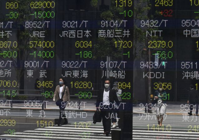 Pedestrians are seen reflected in a quotation board displaying stock prices on the Tokyo Stock Exchange in Tokyo on May 7, 2020.