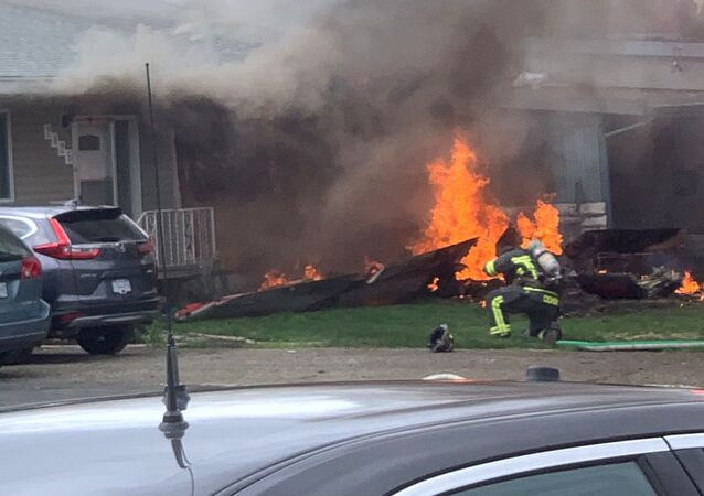 The crash site of a jet from the Canadian air force's Snowbirds aerobatics team is seen in a residential neighbourhood in Kamloops, British Columbia, Canada, May 17, 2020, in this image obtained from social media