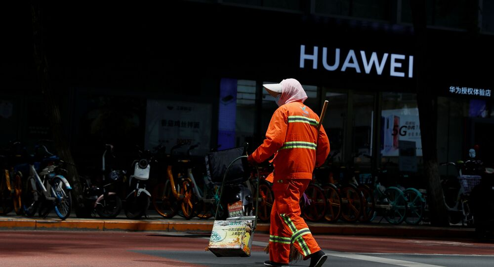 A street cleaner in a face mask walks past a Huawei shop, amid an outbreak of the coronavirus disease (COVID-19), in Beijing, China, May 18, 2020