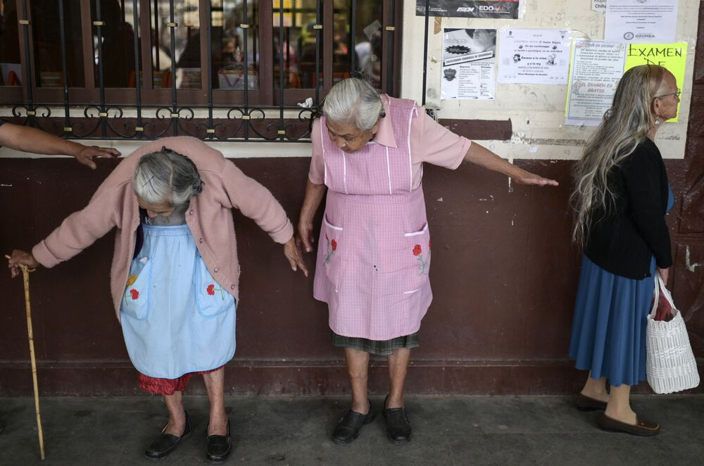 Elderly women maintain distance distance from each other as they wait to enroll in government social aid programmes in downtown Ozumba, Mexico, on 3 April 2020, during the outbreak of the novel coronavirus.
