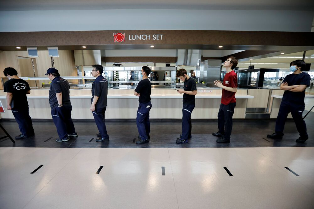 Employees observe social distancing as they order food during their lunch break at the staff canteen while the automaker ramps up car production with new security and health measures as a step to resume full operations, during the outbreak of the coronavirus disease (COVID-19), at the Kawasaki factory of Mitsubishi Fuso Truck and Bus Corp., owned by Germany-based Daimler AG, in Kawasaki, Japan 18 May 2020.