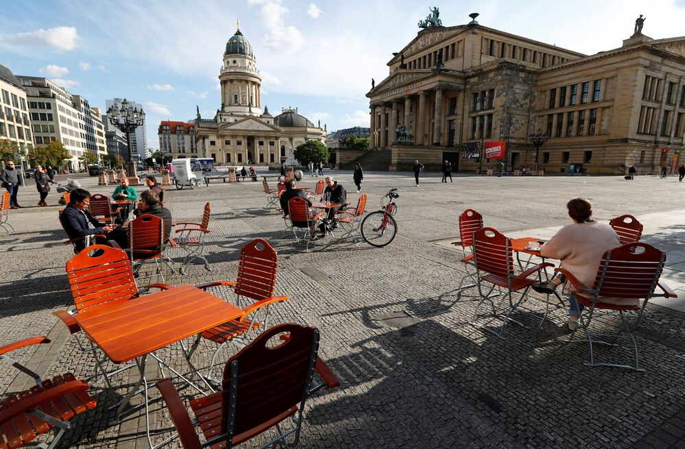 People enjoy the weather at a cafe in Gendarmenmarkt square where social distancing measures are applied, during the coronavirus disease (COVID-19) outbreak, in Berlin, Germany, 16 May 2020.