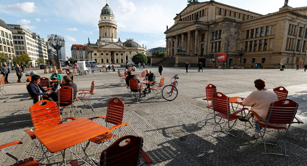 People enjoy the weather at a cafe at Gendarmenmarkt square where social distancing measures are applied, during the coronavirus disease (COVID-19) outbreak, in Berlin, Germany May 16, 2020.