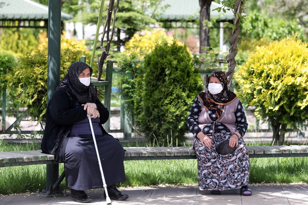 Senior citizens, wearing protective face masks, sit on a bench of a park in the Akyurt district as people over 65 years of age and patients with chronic illnesses across Turkey are allowed to leave their homes, respect a certain distance around their home and wear masks, between 12 a.m. and 6 p.m. local time, in Ankara on 17 May 2020 on the second day of the 4-day hour curfew imposed to stem the spread of the novel coronavirus (COVID-19).
