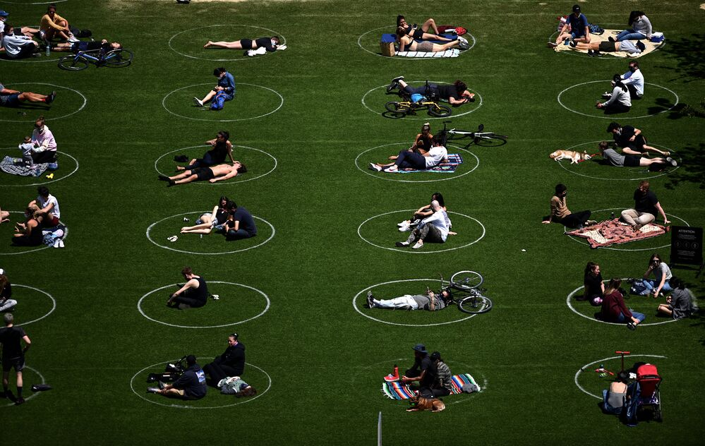 People are seen practising social distancing in white circles in Domino Park, during the COVID-19 pandemic on 17 May 2020 in Brooklyn, New York City.