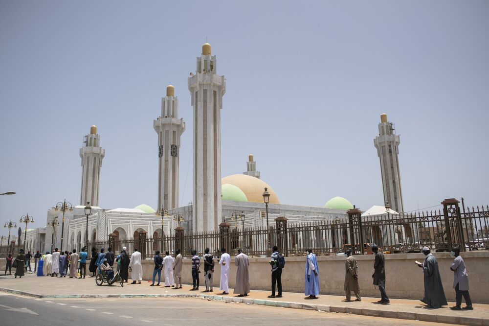 In this photo taken Friday, 15 May 2020, followers of the Senegalese Mouride brotherhood, an order of Sufi Islam, practice social distancing as they queue to attend Muslim Friday prayers at West Africa's largest mosque, the Massalikul Jinaan, in Dakar, Senegal. A growing number of mosques are reopening across West Africa even as confirmed coronavirus cases soar, and  governments find it increasingly difficult to keep them closed during the holy month of Ramadan.