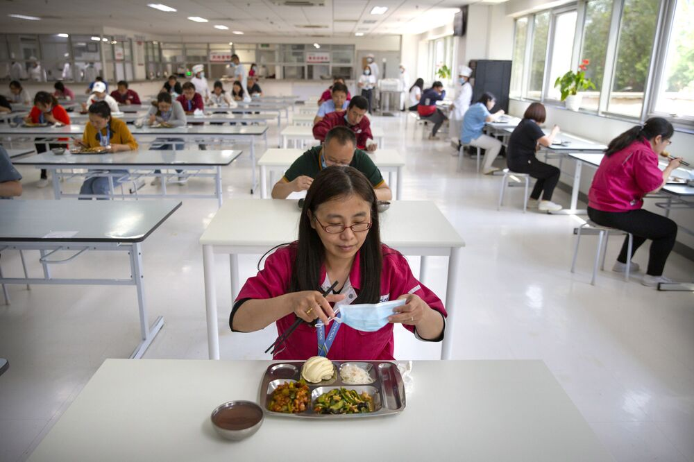 A worker removes her face mask as employees practice social distancing while they eat lunch at a staff cafeteria in a semiconductor production facility for Renesas Electronics during a government organised tour for journalists in Beijing, Thursday, 14 May 2020. China reported three new coronavirus cases Thursday while moving to reopen business and schools.