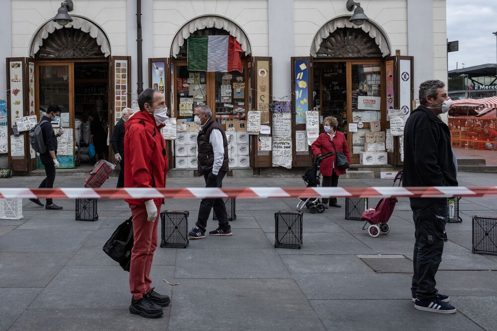 People wait in line at a safe distance to shop at the food market of Porta Palazzo in Turin on 4 May 2020, as Italy starts to ease its lockdown aimed at curbing the spread of the COVID-19 infection. Stir-crazy Italians will be free to stroll and visit relatives for the first time in nine weeks on 4 May 2020 as Europe's hardest-hit country eases back the world's longest nationwide coronavirus lockdown.