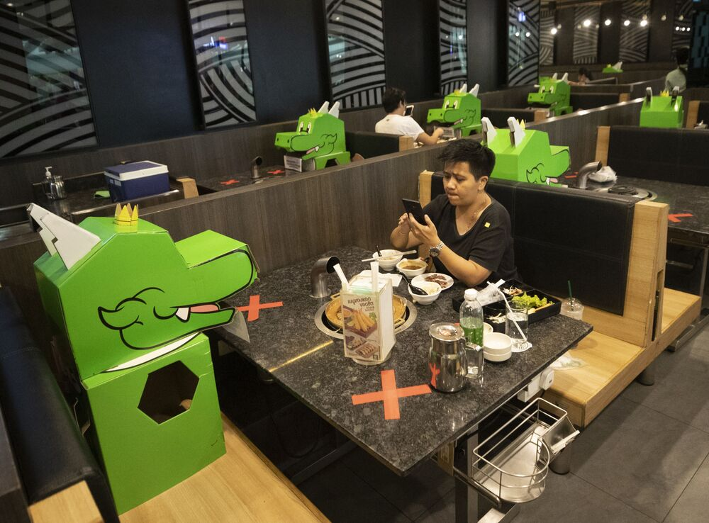 A customer uses a mobile phone while sitting with a cartoon dragon doll the restaurant uses as space holders for social distancing to help curb the spread of the coronavirus at a shopping mall in Bangkok, Thailand, Monday, 18 May 2020. Thai authorities allowed department stores, shopping malls, and other businesses to reopen from 17 May, selectively easing restrictions meant to combat the coronavirus.