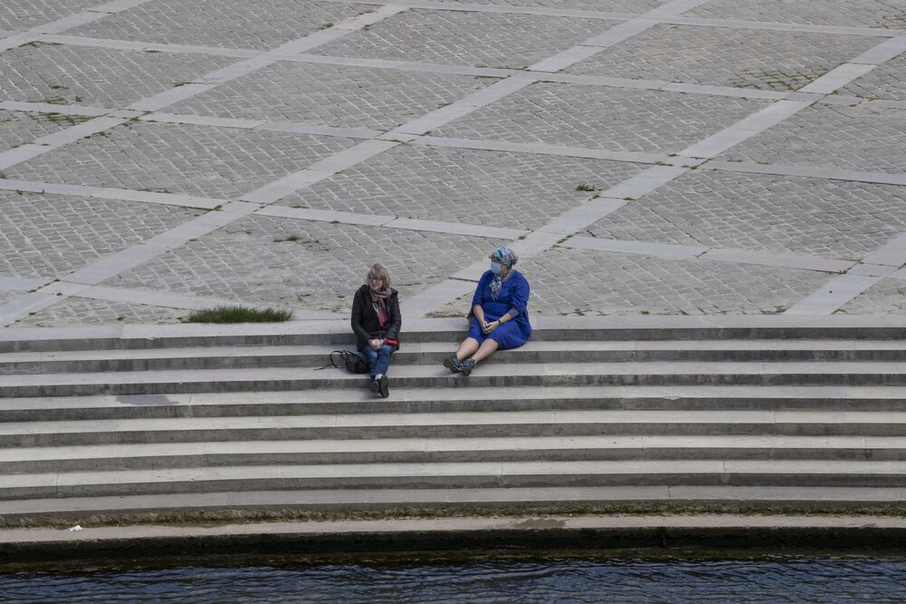 Two women, one wearing a face mask to help curb the spread of the coronavirus sit along the Seine  in Paris, Thursday, 14 May 2020. France is cautiously easing the two-month lockdown across the country. Specific measures, such as more widely spaced stalls, have been implemented to enforce physical distancing.