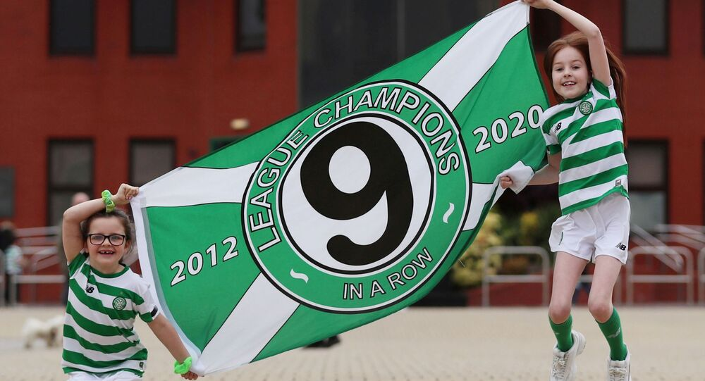 Fans are seen with a flag outside Celtic Park after Celtic were confirmed champions after the SPFL ended the season, following the outbreak of the coronavirus disease (COVID-19), Glasgow, Britain, May 18, 2020.