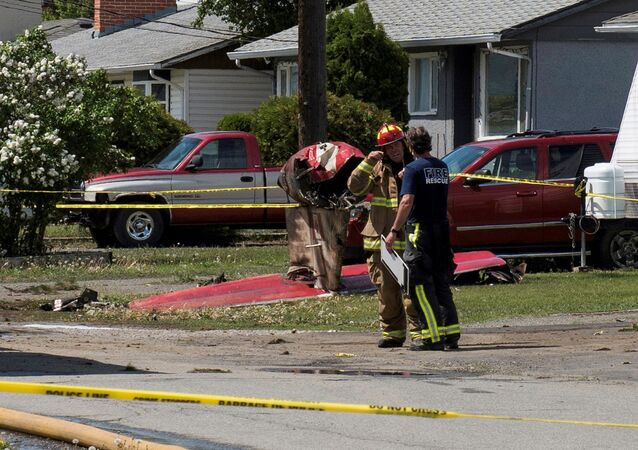 Fire officials talk in a residential neighbourhood street in front of the tail wreckage from a Royal Canadian Air Force Snowbirds jet after a member of the exhibition team crashed shortly after takeoff in Kamloops, British Columbia, Canada May 17, 2020.