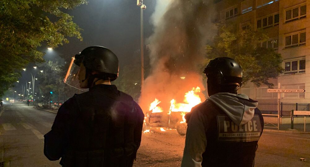 Riot police look on against the backdrop of a car that was set on fire on 18 May during protests against the death of an 18-year-old motorcyclist in Argenteuil, Paris.