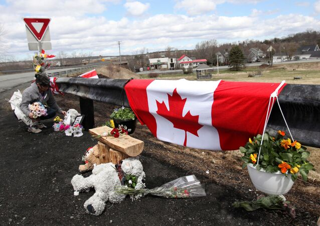 Krista Hughes adjusts flowers that had blown away from a makeshift memorial for Royal Canadian Mounted Police (RCMP) Constable Heidi Stevenson, who was shot dead during Sunday's killing spree that worked it's way across several Nova Scotian communities, in Shubenacadie, near Enfield, Nova Scotia, Canada April 22, 2020.