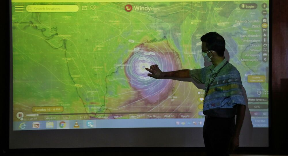 A scientist at India Meteorological Department Earth System Science Organisation, points to a section of the screen showing the position of the Cyclone Amphan to media people inside his office in Kolkata, India, May 19, 2020