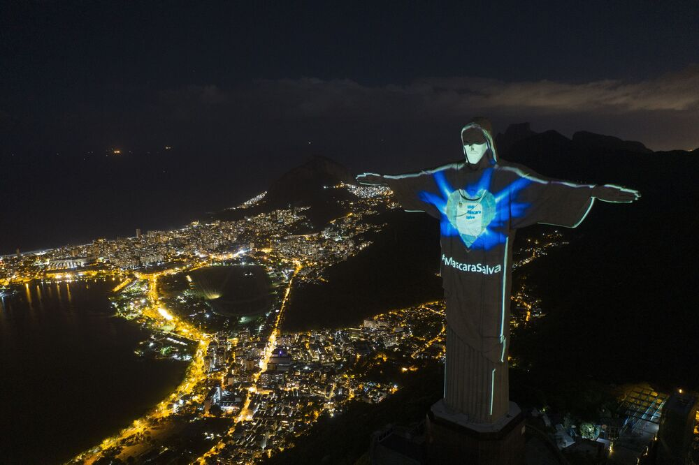 In this 3 May 2020 photo, the iconic Christ the Redeemer statue is lit up as if wearing a protective mask and features a hashtag that reads Mask saves in Portuguese, amid the new coronavirus pandemic in Rio de Janeiro, Brazil.