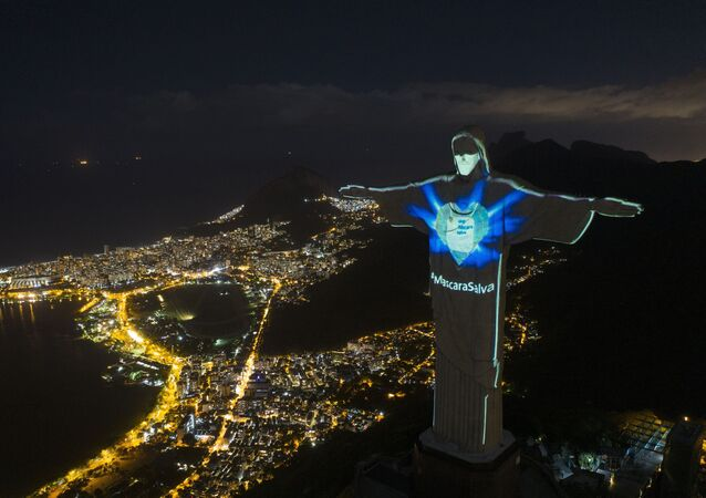 In this Sunday, May 3, 2020 photo, the iconic Christ the Redeemer statue is lit up as if wearing a protective mask and with a hashtag that reads in Portuguese: Mask saves, amid the new coronavirus pandemic, in Rio de Janeiro, Brazil.