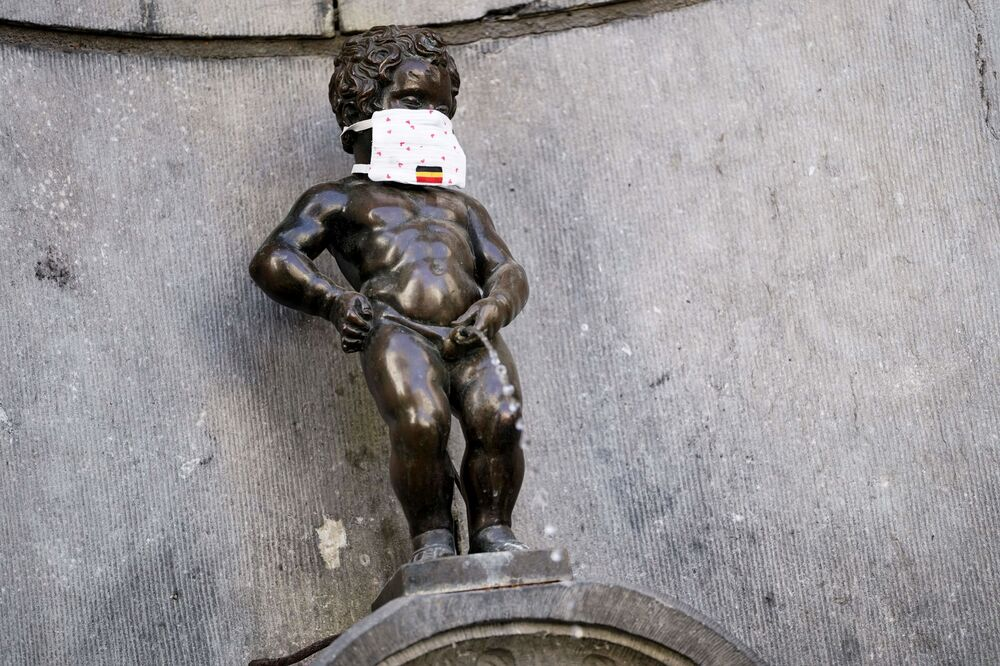 This picture taken on 11 May 2020 in Brussels shows a  face mask set on the Manneken-Pis statue to help compel people to wear a mask in public, on the first day of a partial lifting of the lockdown introduced two months ago to fight the spread of COVID-19.