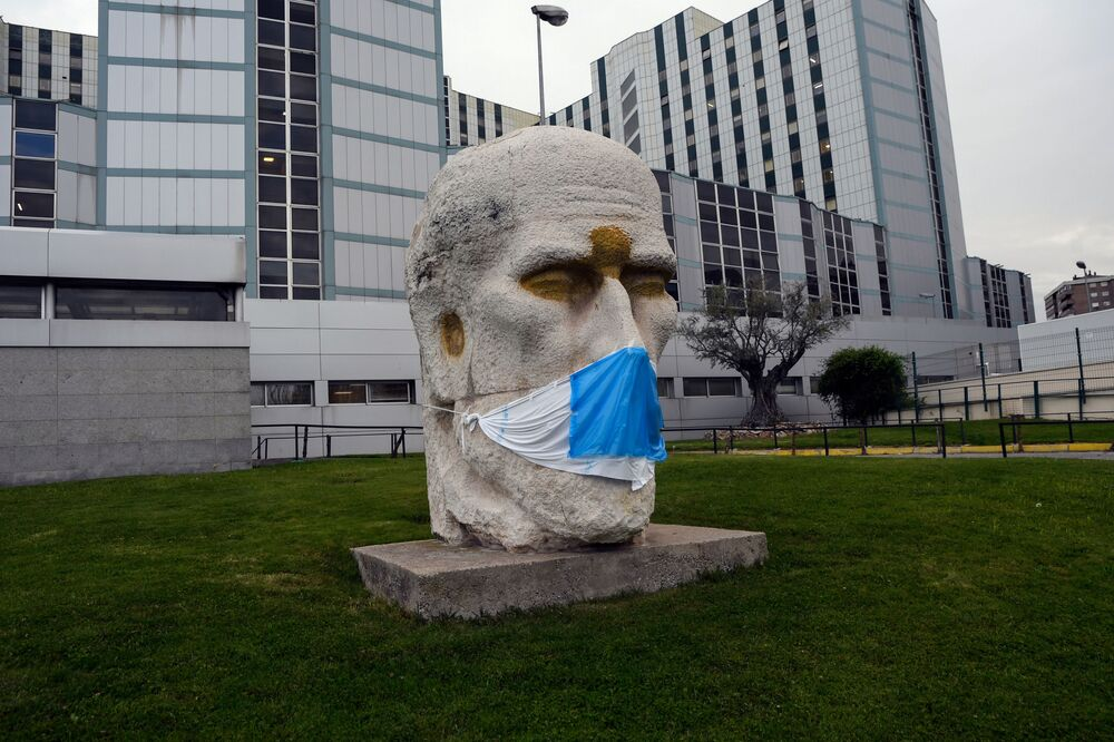 A face mask is placed on the statue of Spanish neuroscientist Santiago Ramon y Cajal by sculptor Eduardo Carretero outside the Ramon y Cajal Hospital in Madrid on 14 April 2020.