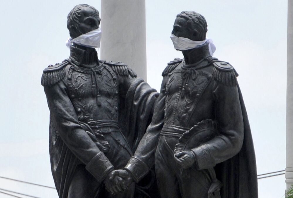 View of the monument to Liberators Simon Bolivar and Jose de San Martin, both wearing face masks, in Guayaquil, Ecuador, on 14 April 2020 during the COVID-19 pandemic.