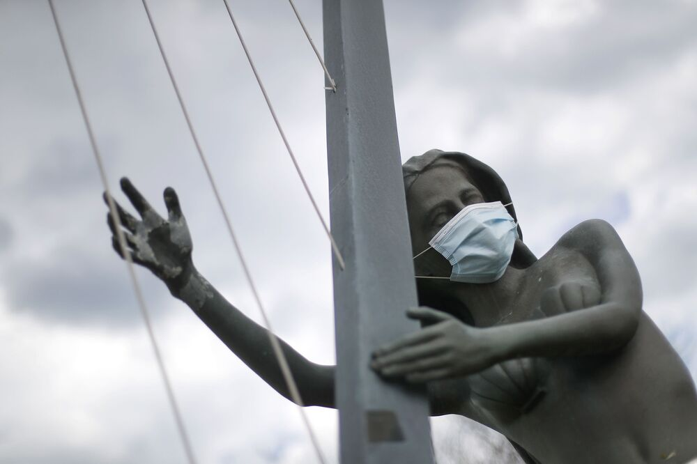 A protective mask is shown on a statue of a mermaid playing harp in St. Clair Shores, Michigan, US on 7 May 2020.