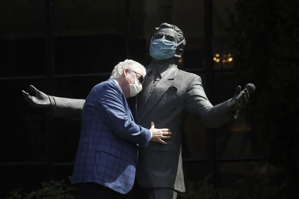 Paul Tormey, Regional Vice President of Fairmont Hotels, wears a mask while hugging a statue of singer Tony Bennett outside of the Fairmont San Francisco hotel before leading hotel workers in a singing of the song I Left My Heart in San Francisco, 25 April 2020, in San Francisco.
