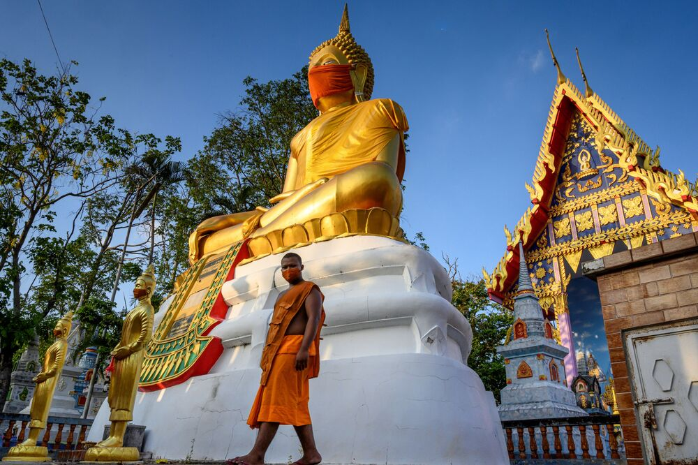 A monk walks in front of a giant Buddha statue wearing a face mask at Wat Nithet Rat Pradit temple in Pathum Thani outside Bangkok on 12 May 2020