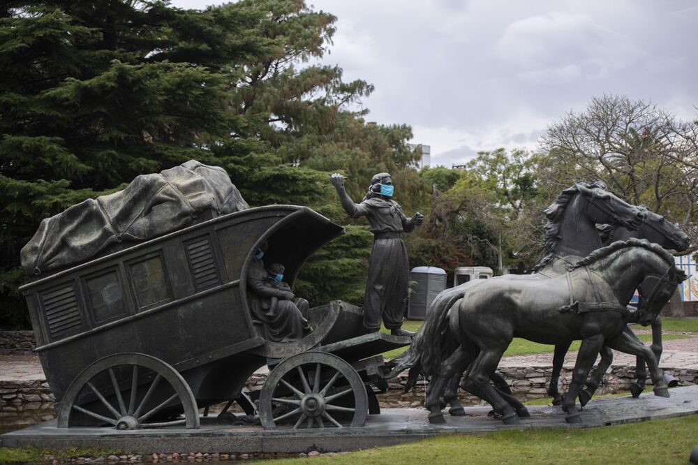 A statue of a gaucho family wearing face masks as if to prevent the spread of new coronavirus stands in Montevideo, Uruguay, 4 May 2020. The sculpture is part of a larger set which represents the pioneers in Uruguay and is called The Stage Coach. It was created by Uruguayan sculptor Jose Belloni in 1922