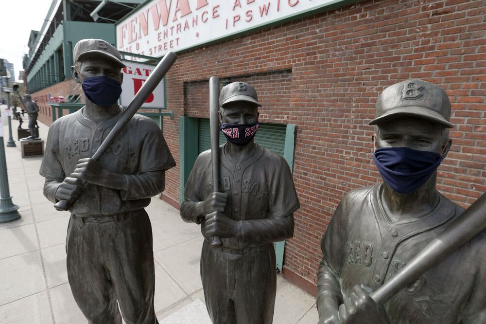 Statues of former Boston Red Sox greats, from left, Ted Williams, Bobby Doerr and Johnny Pesky, wear protective masks outside Fenway Park, 17 April 2020, in Boston.