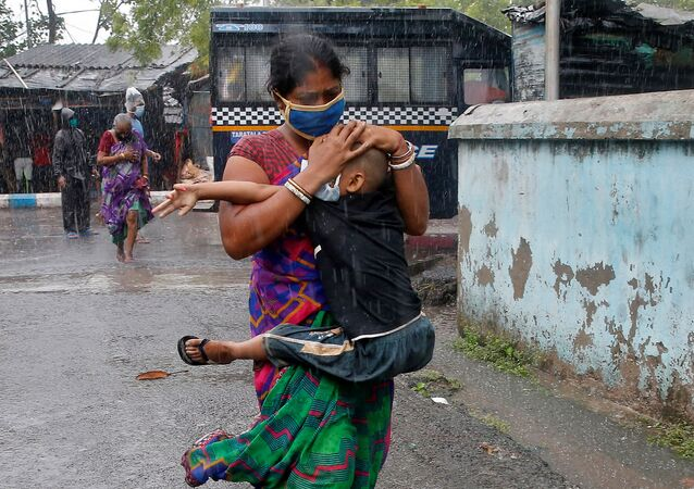 A woman carries her son as she tries to protect him from heavy rain while they rush to a safer place, following their evacuation from a slum area before Cyclone Amphan makes its landfall, in Kolkata, India, May 20, 2020