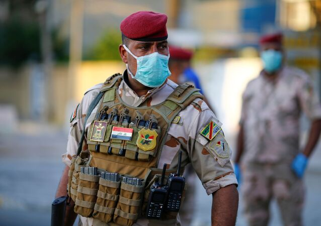 An Iraqi soldier wears a protective face mask as he stands guard at a check point, enforcing a curfew imposed to prevent the spread of the coronavirus disease (COVID-19), during the holy fasting month of Ramadan, in Baghdad, Iraq May 3, 2020