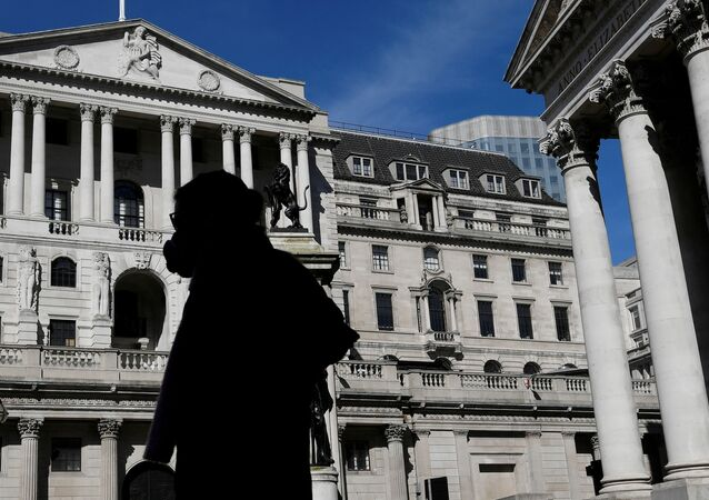 People wearing masks walk past the Bank of England, as the spread of the coronavirus disease (COVID-19) continues, in London, Britain, March 23, 2020.