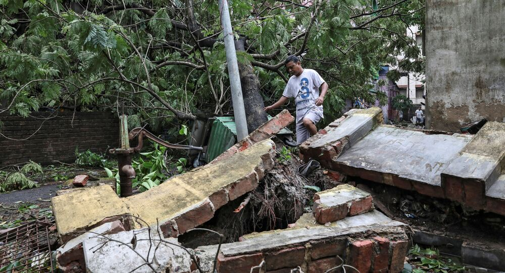 A man walks over a collapsed wall after Cyclone Amphan made its landfall, in Kolkata, India, May 21, 2020.