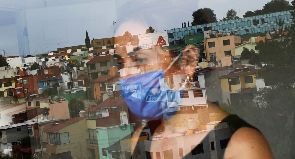 Monica Samudio, 46, whose husband Jorge Garcia, 51, died from the coronavirus disease (COVID-19), is reflected in the window as she looks out of her new apartment, in Mexico City, Mexico April 29, 2020
